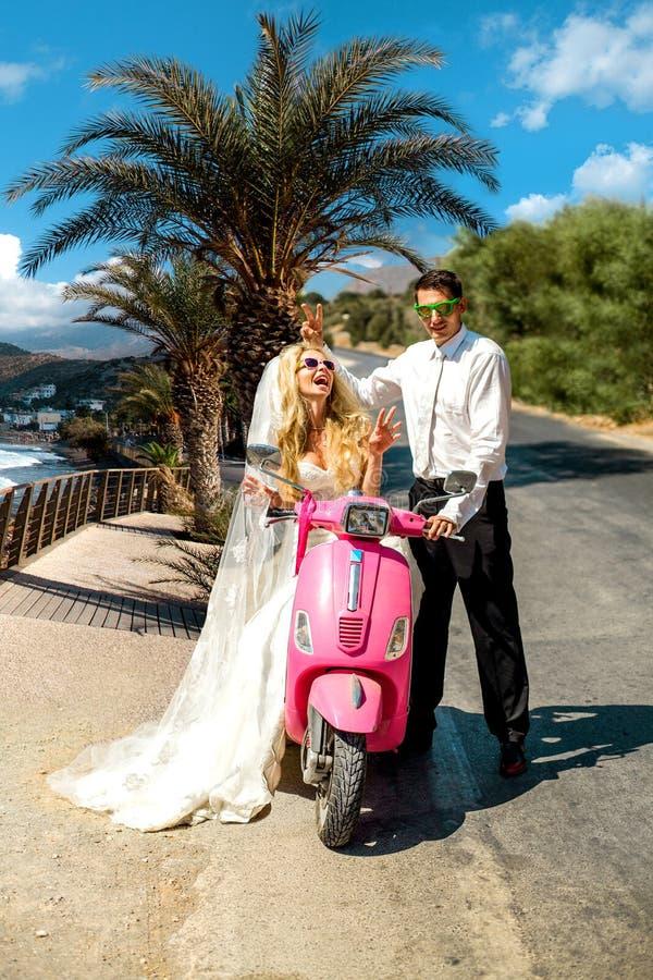 Le beau jeune couple, modèle femelle blond avec son mari dans le mariage étonnant vêtx se reposer sur le scooter image stock