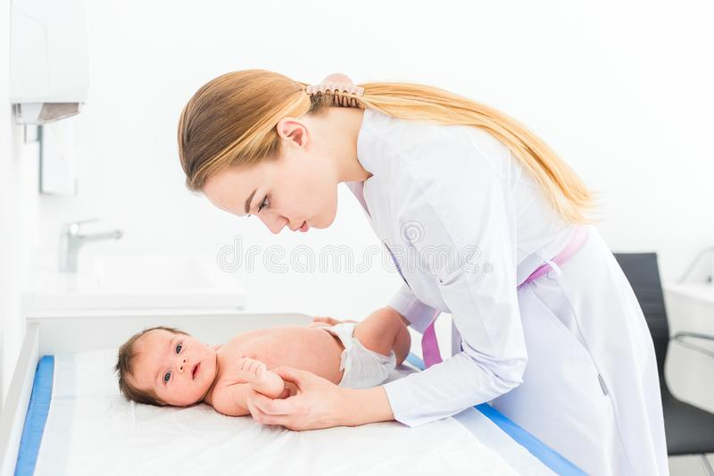 Le beau jeune docteur blond féminin de pédiatre examine le bébé vérifiant sa peau photos stock