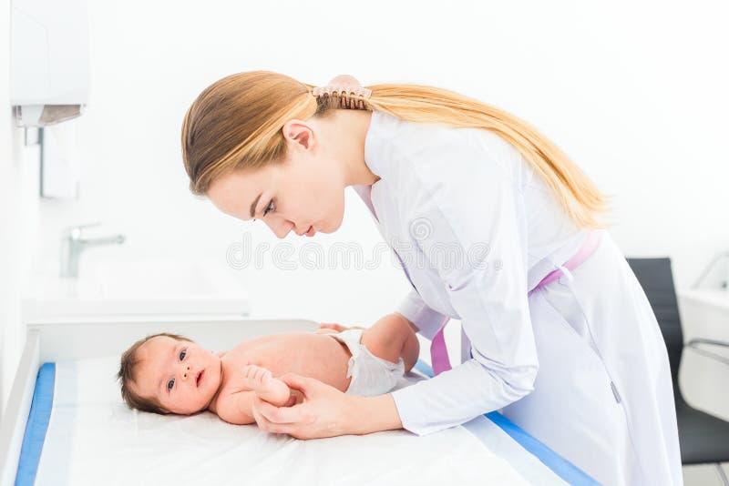 Le beau jeune docteur blond féminin de pédiatre examine le bébé vérifiant sa peau images stock
