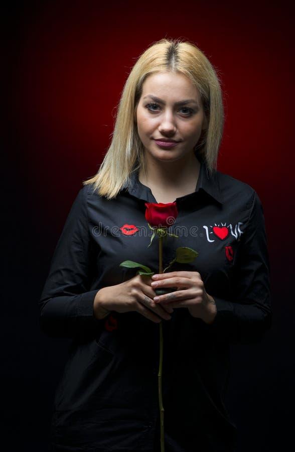 Le beau jeune femme avec le rouge s'est levé photo stock