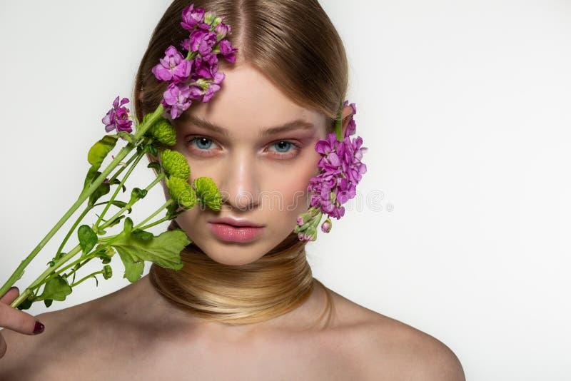 Le beau jeune mod?le femelle avec des yeux bleus, peau parfaite avec des fleurs sur l'?paule, son cou est envelopp? dans les chev photographie stock
