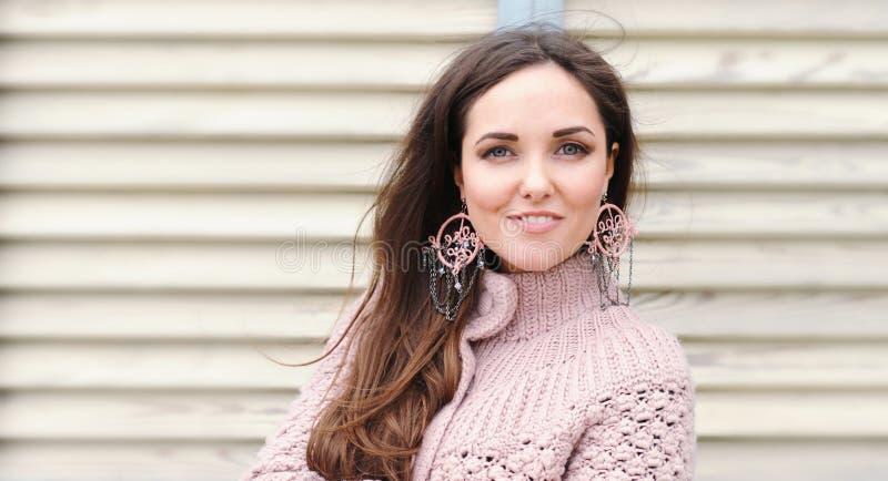 Le beau jeune portrait heureux de femme, le chandail doux mignon et le boho fait main dénomment des boucles d'oreille photographie stock