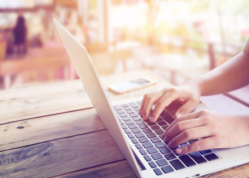le beau jeune ` s de femme de hippie remet travailler occupé sur son ordinateur portable se reposant à la table en bois dans un c images stock