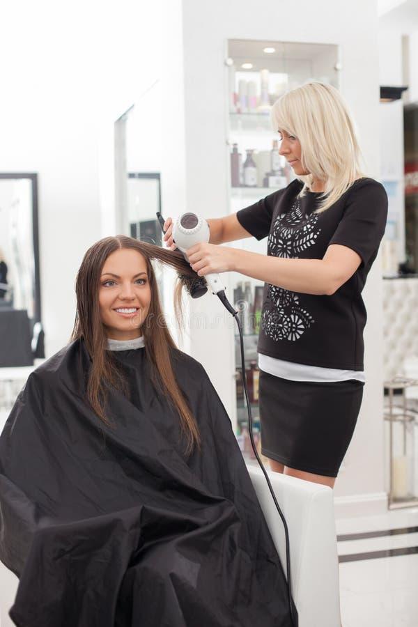 Le beau jeune styliste en coiffure sert son client image libre de droits