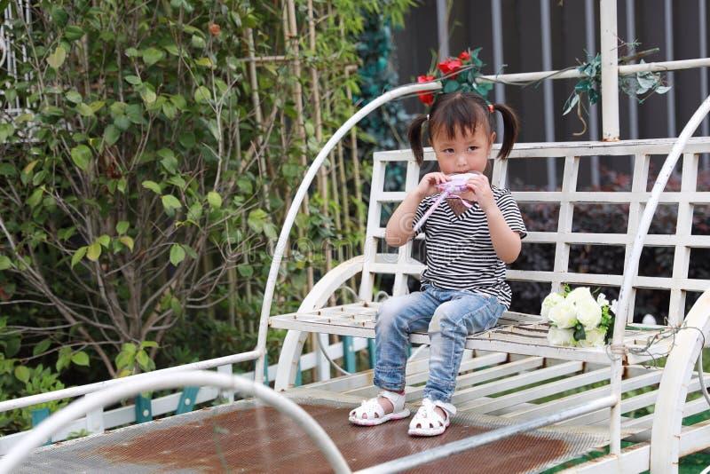 Le beau lolipop adorable vilain mignon heureux de jeu de petite fille et se reposent sur un chariot ont l'amusement extérieur dan image stock