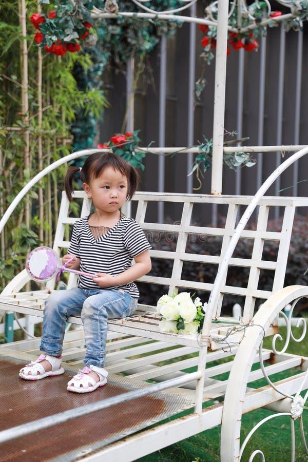 Le beau lolipop adorable vilain mignon heureux de jeu de petite fille et se reposent sur un chariot ont l'amusement extérieur dan photographie stock