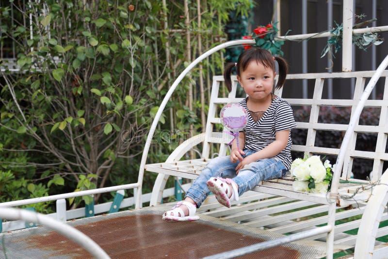 Le beau lolipop adorable vilain mignon heureux de jeu de petite fille et se reposent sur un chariot ont l'amusement extérieur dan photo libre de droits