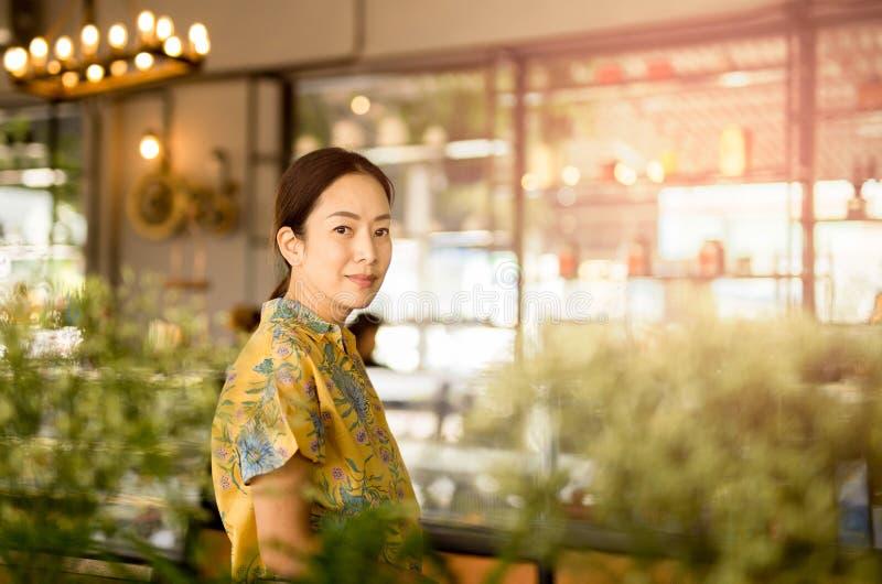 Le beau milieu a vieilli la femme asiatique regardant la caméra dans le café photo libre de droits