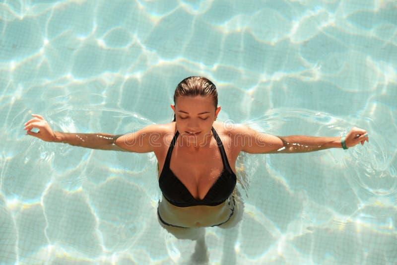 Le beau modèle de fille de brune détendent dans un bain noir de maillot de bain photo libre de droits