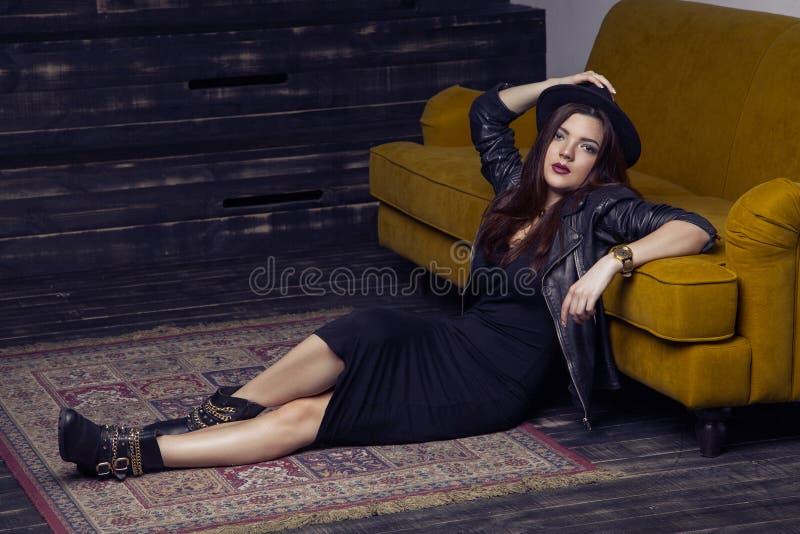 Le beau modèle du Moyen-Orient de mode avec le style de hippie pose sur le tapis et le sofa jaune images stock