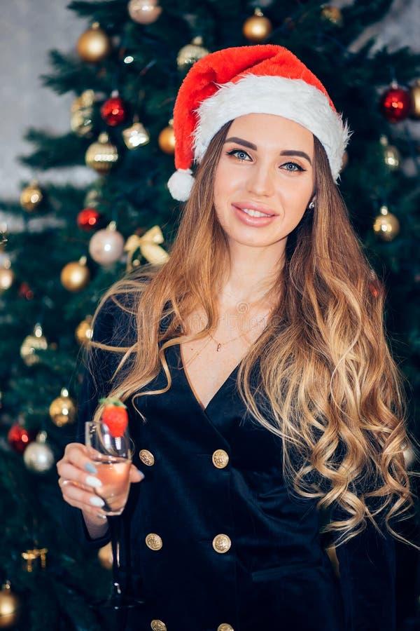 Le beau modèle femelle utilisent le chapeau de Santa avec le verre de champagne Portrait d'une fille dans une robe noire, fin  images libres de droits