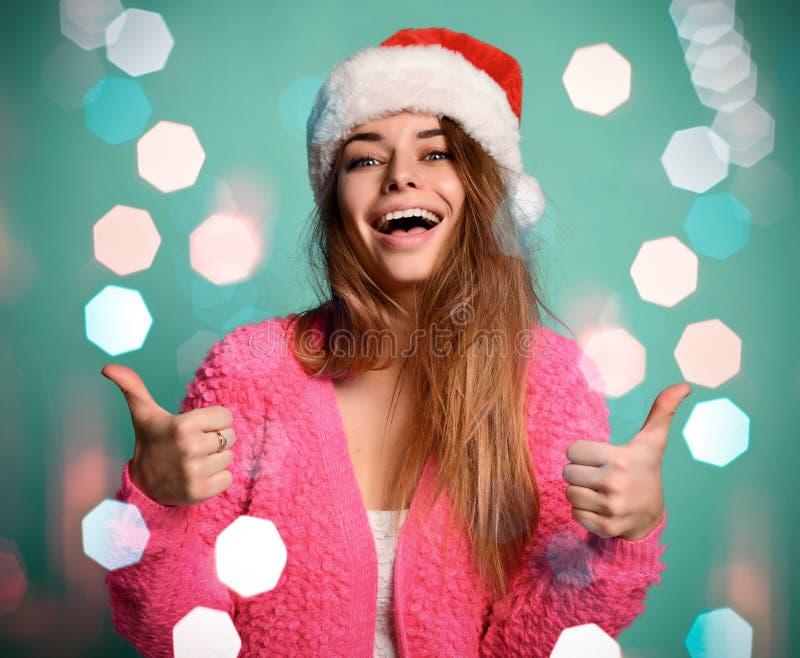 Le beau modèle femelle utilisent les pouces de sourire heureux d'apparence de chapeau de Noël Santa sur la menthe bleue images stock