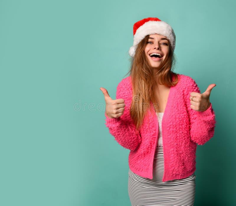 Le beau modèle femelle utilisent les pouces de sourire heureux d'apparence de chapeau de Noël Santa sur la menthe bleue image libre de droits