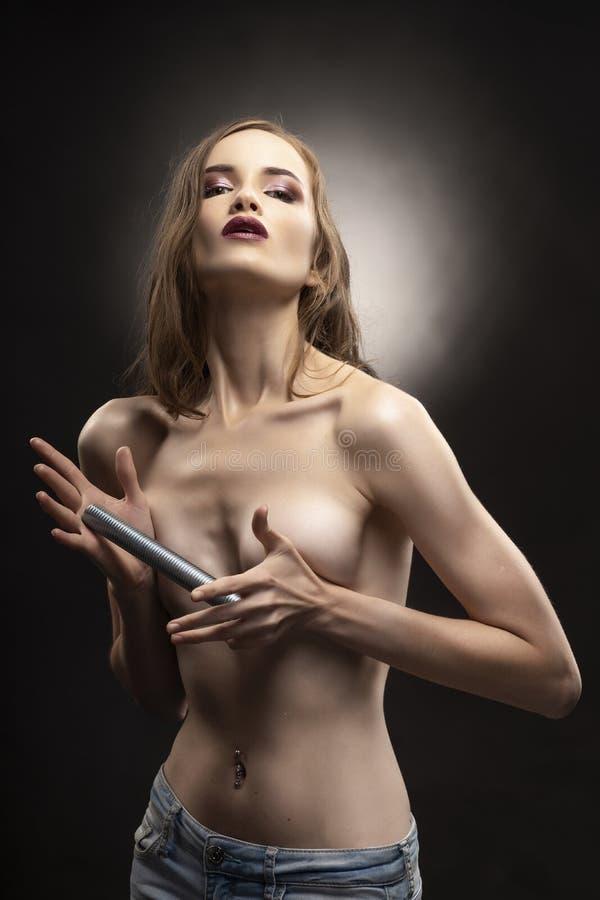 Le beau modèle sportif mince de fille de torse nu juge dans des ses mains photographie stock