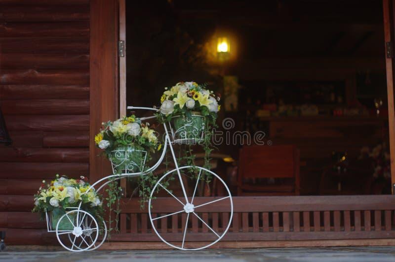 Le beau panier de fleur sur la bicyclette se garent devant la porte photo stock