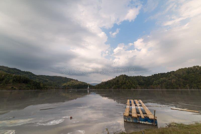 Le beau paysage avec un pont en bois et une église submergée au-dessus de toxique a pollué le lac dû à l'exploitation de cuivre images stock