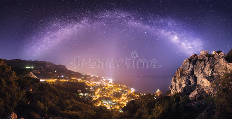 Le beau paysage de nuit avec la manière laiteuse contre la ville s'allume photographie stock libre de droits