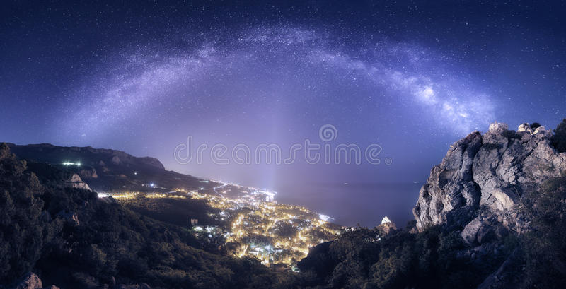 Le beau paysage de nuit avec la manière laiteuse contre la ville s'allume image stock