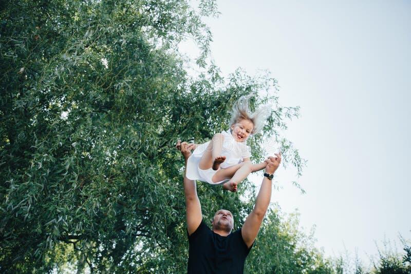 Le beau petit bébé blond a le visage de sourire d'amusement heureux jouant dans une robe blanche avec son papa, enfant et père images libres de droits