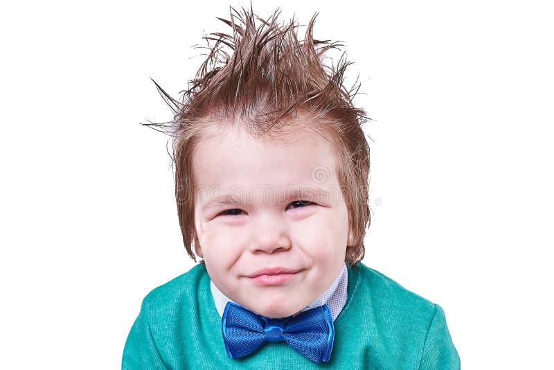 Le beau petit garçon dans le noeud papillon bleu et le chandail vert, et elle fait les visages drôles d'isolement sur le fond bla photo stock