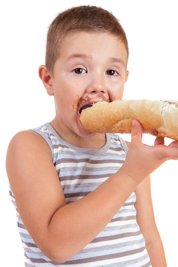 Le beau petit garçon mange du pain avec du Cr de chocolat photo libre de droits