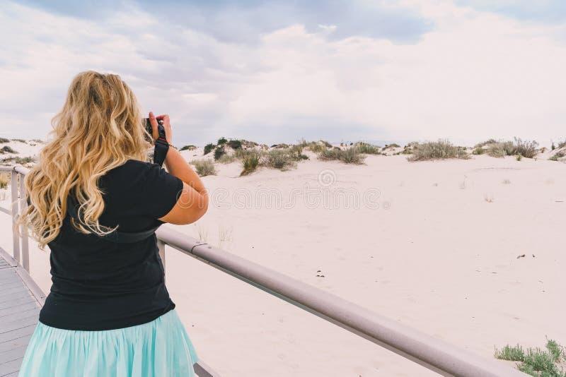 Le beau photographe féminin blond prend des photos sur la promenade aux dunes de sable photos libres de droits