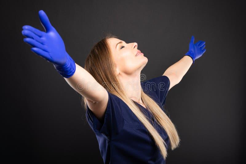 Le beau port femelle de dentiste frotte faire le geste de gagnant photo stock
