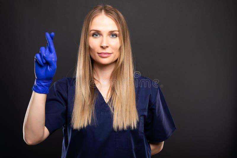 Le beau port femelle de dentiste frotte montrant des doigts croisé photographie stock