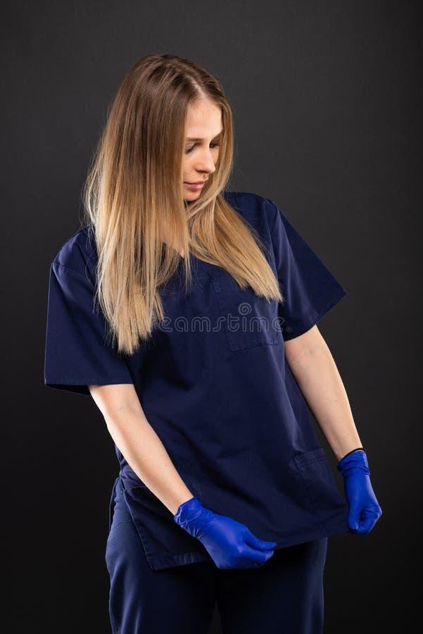 Le beau port femelle de dentiste frotte s'charger de la chemise image stock