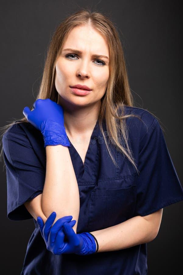 Le beau port femelle de docteur frotte faire le geste de douleur de coude photographie stock libre de droits