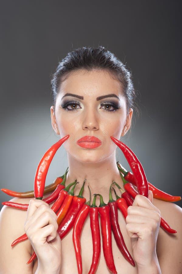 Le beau portrait de jeune femme avec les poivrons d'un rouge ardent et épicés, mannequin avec le légume créatif de nourriture com photographie stock libre de droits