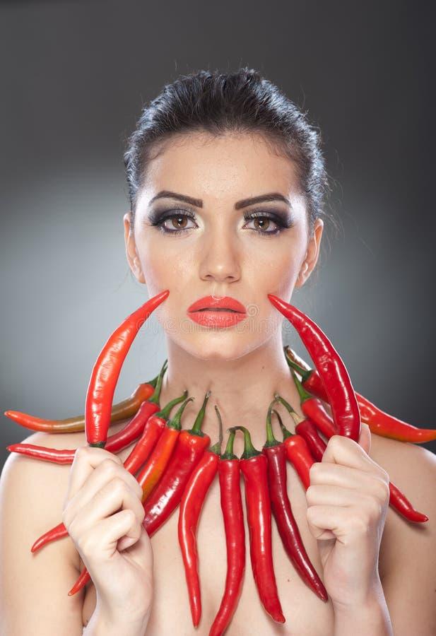 Le beau portrait de jeune femme avec les poivrons d'un rouge ardent et épicés, mannequin avec le légume créatif de nourriture com image libre de droits