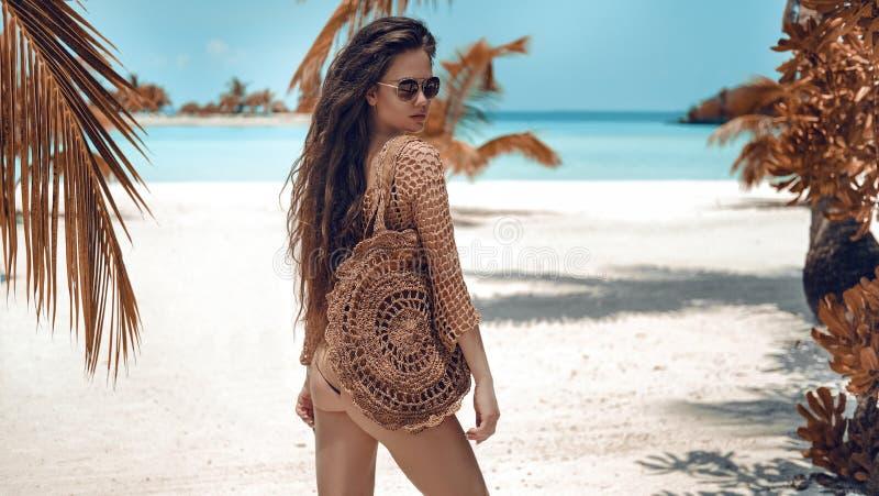 Le beau portrait de luxe de la femme de brune dans beige tricotent le maillot de bain de crochet posant par l'eau d'océan r images libres de droits