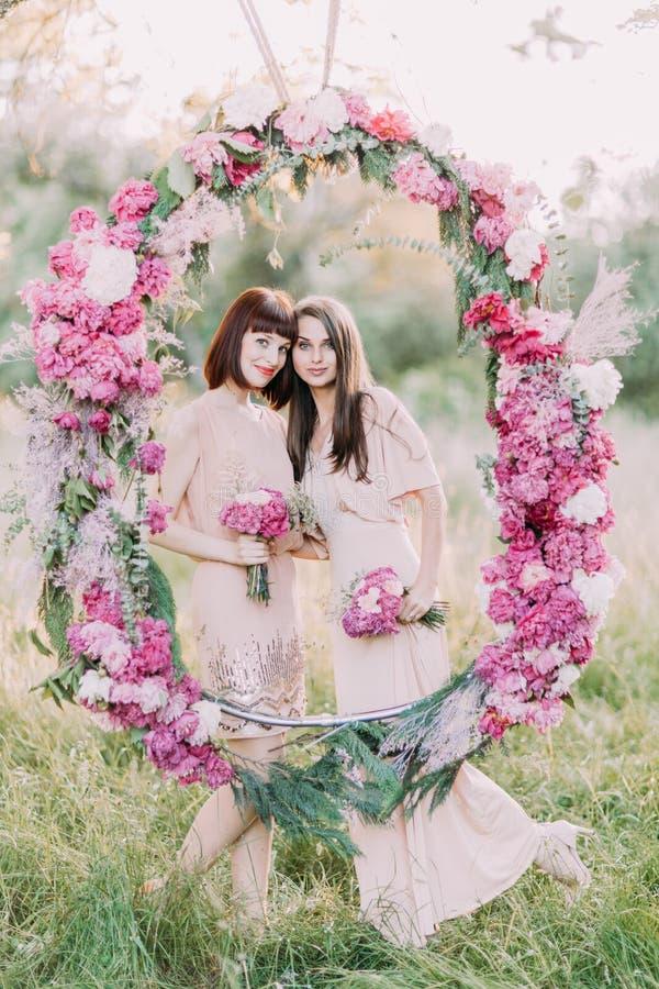 Le beau portrait des deux demoiselles d'honneur tenant les bouquets des fleurs roses et de la position derrière les pivoines de m photos libres de droits