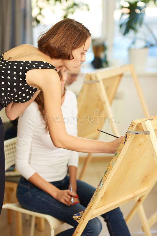 Le beau professeur de dessin aide la jeune jolie fille avec les cheveux boucl?s bruns ? peindre un tableau au chevalet dans photographie stock libre de droits