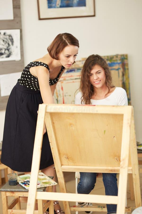 Le beau professeur de dessin aide la jeune jolie fille avec les cheveux boucl?s bruns ? peindre un tableau au chevalet dans photos libres de droits