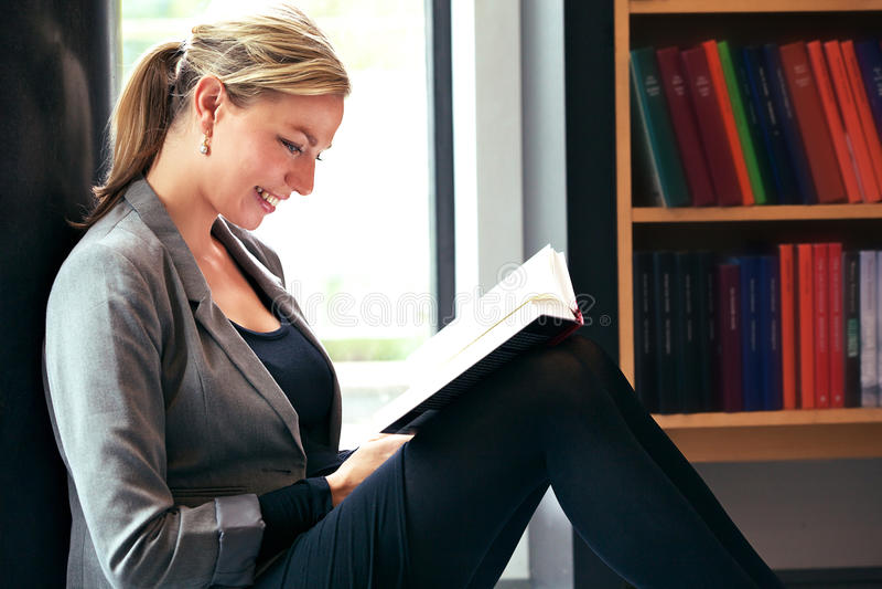 Le beau relevé de femme dans la bibliothèque photo libre de droits