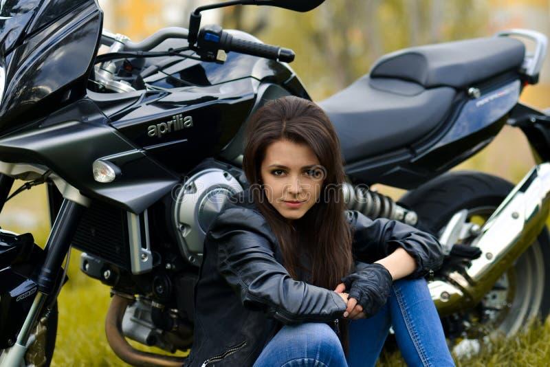 Le beau, sérieux, dangereux patron professionnel, fille de cycliste, chef se repose près du noir, le meilleur vélo, motocyclette  photographie stock libre de droits