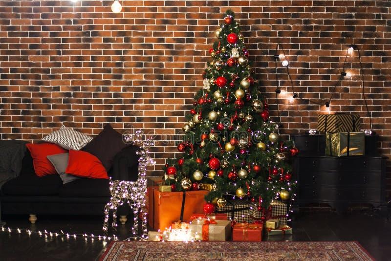 Le beau salon de Noël avec l'arbre de Noël, les cadeaux et les cerfs communs décorés avec rougeoyer s'allume la nuit Inte de gren photo libre de droits