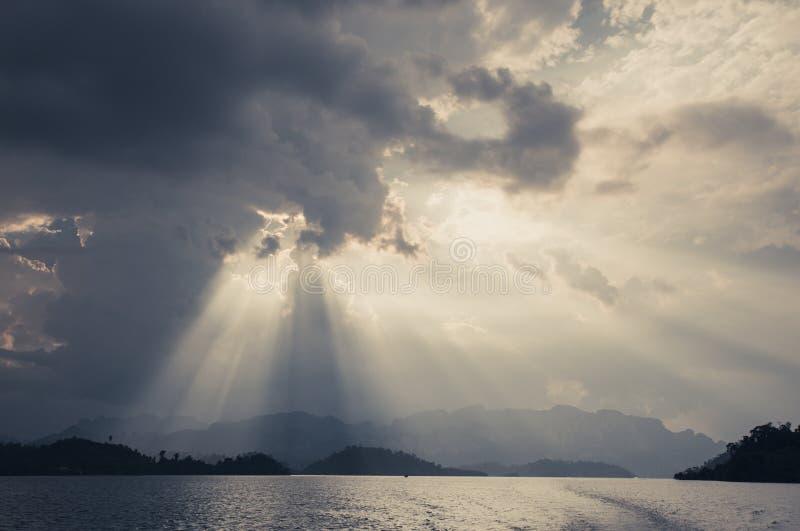 Le beau soleil rayonne par les nuages au-dessus des montagnes, égalisant le lig images libres de droits