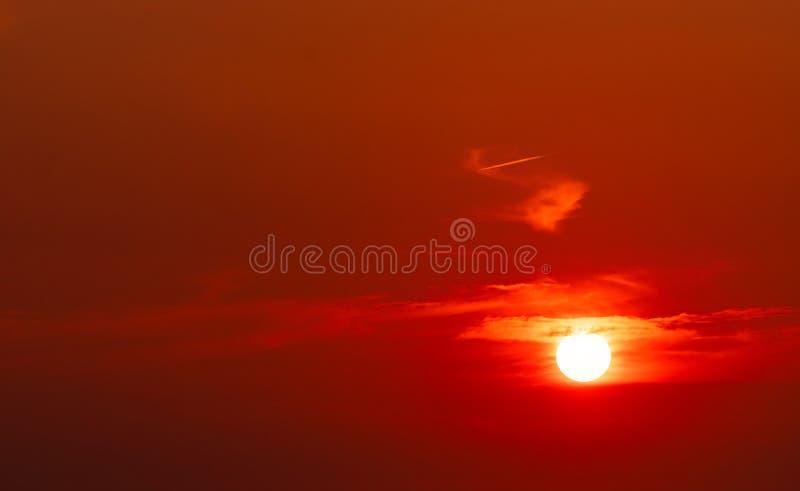 Le beau soleil rouge au coucher du soleil Ciel rouge de coucher du soleil Le soleil est obscurci par quelques nuages au coucher d images libres de droits