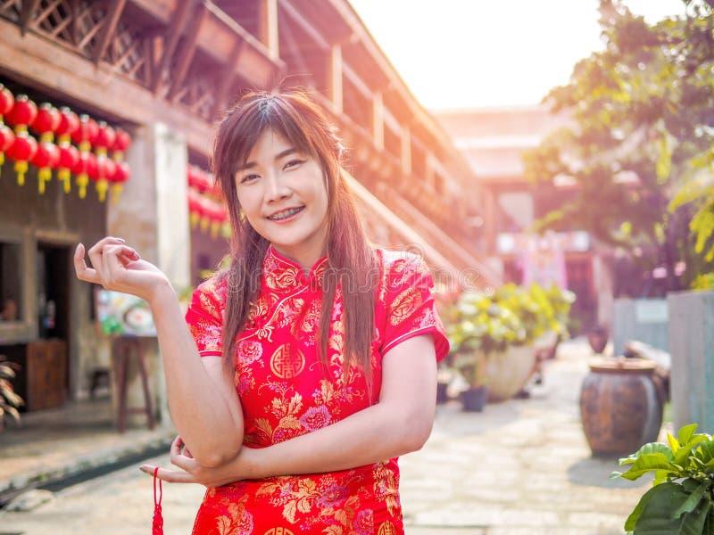 Le beau sourire de jeune femme portent la robe rouge-foncé de cheongsam regardant la caméra An neuf chinois photographie stock libre de droits