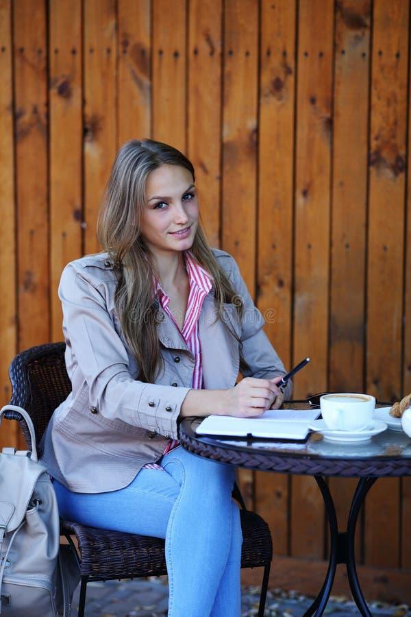 Le beau stylo de participation de fille se reposent près de la table images stock