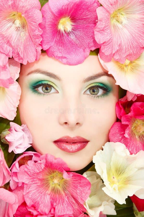 Le beau visage femelle avec la mauve rose, rouge et blanche fleurit le franc image libre de droits