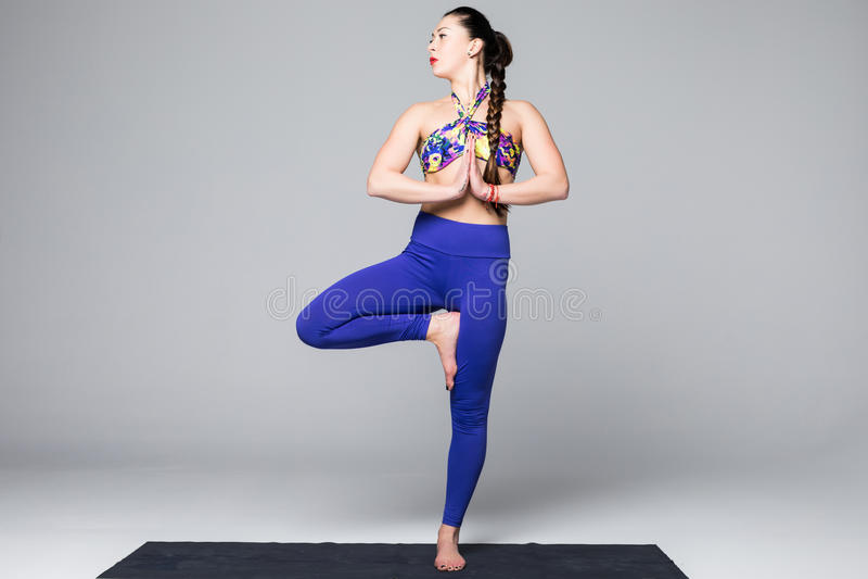 Le beau yoga de pratique en matière de femme de yoga pose sur le fond gris image stock