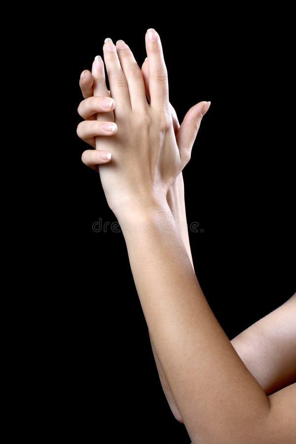 Le beau ypung remet la femme d'isolement sur le fond noir image stock