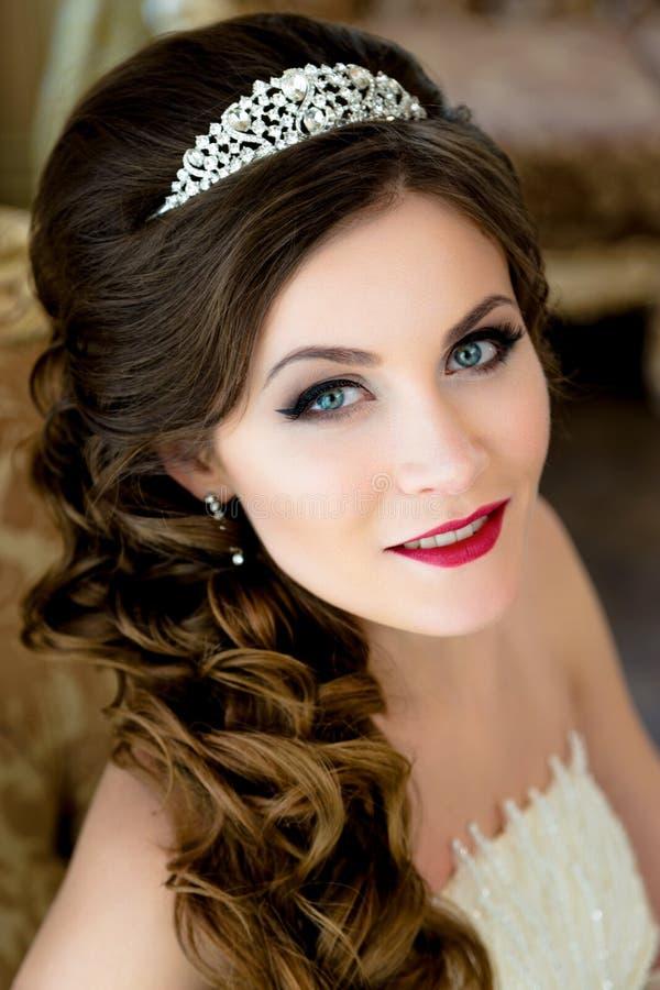 Le beaux maquillage et coiffure de mariage de portrait de jeune mariée de brune avec le diamant couronnent photos stock