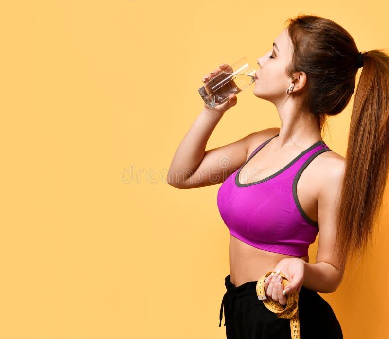 Le beaux ruban métrique et boisson de prise de femme de sports arrosent le concept de la vie de perte de poids images libres de droits