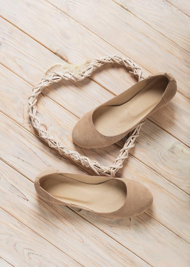Le ` beige s de femmes chausse des ballerines sur le fond en bois image stock