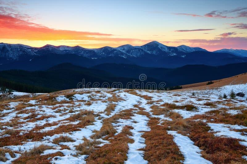 Le bel éclat rose de coucher du soleil éclaire les paysages pittoresques avec l'herbe jaune juste et les hautes montagnes images stock